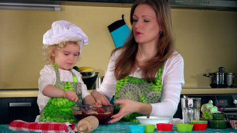 Caucasian woman and cute daughter cooking in kitchen. Family girls having fun Footage