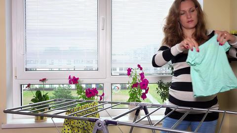 Pregnant woman hang laundry at home ビデオ