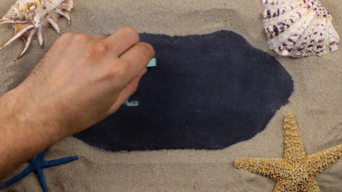 Handwritten word GELENDZHIK written in chalk, among seashells and stars. Top Footage