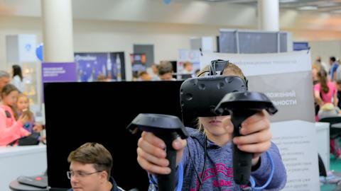 Teenager girl using virtual reality headset at technology show ビデオ