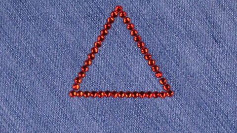 Rotation of a triangle made of red rhinestones on denim, the triangle symbolizes Live Action