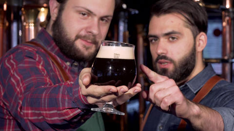 Selective focus on a glass of dark beer in hands of a brewer ライブ動画