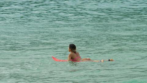 Attractive surfer woman on a surfboard floating in ocean ビデオ