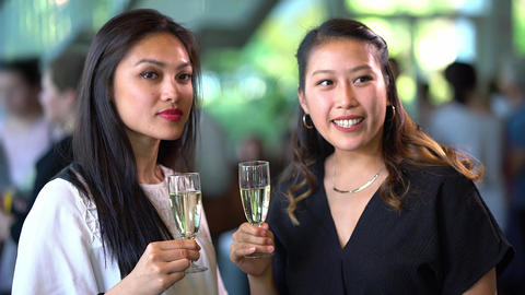 Two Asian girls drink champagne on a party - exclusive event Footage