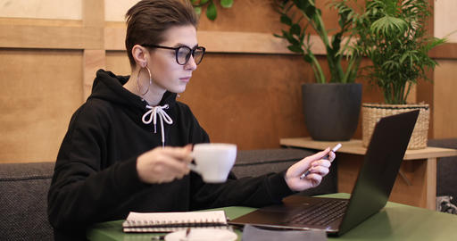 Casual Girl Drinking Coffee and Using Laptop Footage