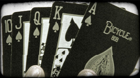 A royal flush of spades folded out from behind an ace. Vintage stylized video cl Live Action