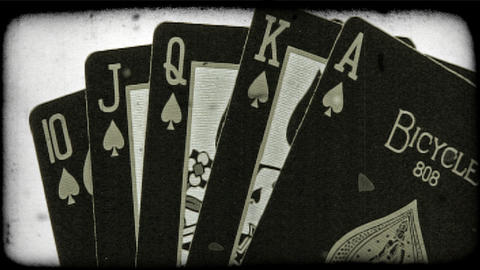 A royal flush of spade face cards rotate into view. Vintage stylized video clip Footage