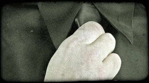 A close up of a hand straightening a tie. Vintage stylized video clip Footage