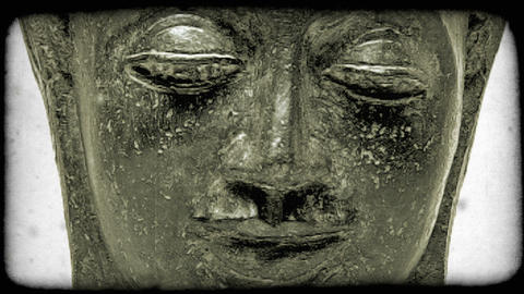 Zooming out shot of a Buddha's face. Vintage stylized video clip Footage