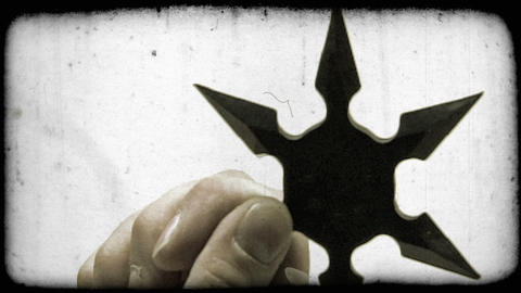 Close-up shot of a shuriken in a person's hand. Vintage stylized video clip Footage