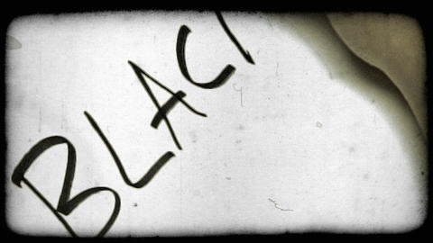 Close-up shot of a person's hand writing the word black. Vintage stylized video  Footage