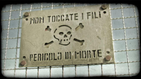 Static shot of a warning sign on an electric fence in Italy. Vintage stylized vi Footage