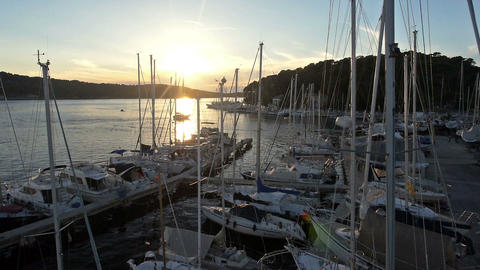 Aerial - Flight past and above the masts of sailboats in marina at sunset Footage