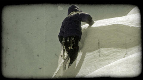 Man climbs up snowy hill. Vintage stylized video clip Footage