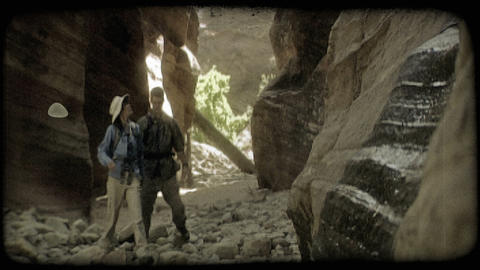 Couple hikes through canyon. Vintage stylized video clip Footage