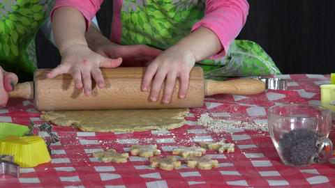 little mother helper girl is helping to roll dough batter on kitchen table GIF
