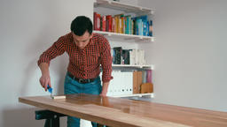Man in a Checkered Shirt is Finishing Wooden Oak Table with a Roller at Home ビデオ