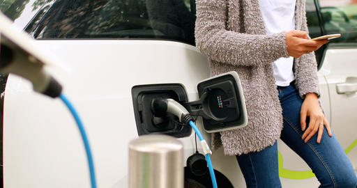 Woman using mobile phone while charging electric car at charging station 4k Live Action