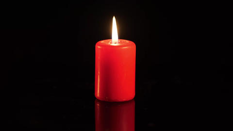 Small flame on a candle black background Footage