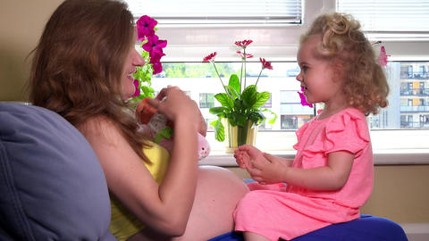 pregnant mother and blond girl care toy baby doll at home Footage