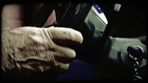 Static shot of elderly person's hands on a steering wheel. Vintage stylized vide Footage