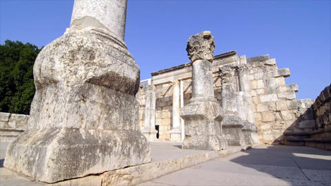 Slow-moving tracking footage of ruined columns near crumbling wall Footage