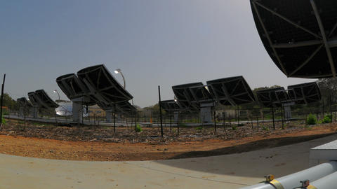 Panning shot of Time-lapse shot behind an array of solar collectors tracking the Footage