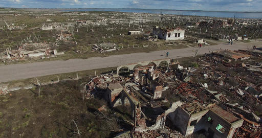 Aerial drone scene of abandoned, demolished town. Camera travels fast through th Footage