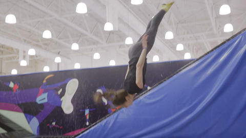 Young fit happy woman jumping and flying on trampoline in fitness gym Live Action