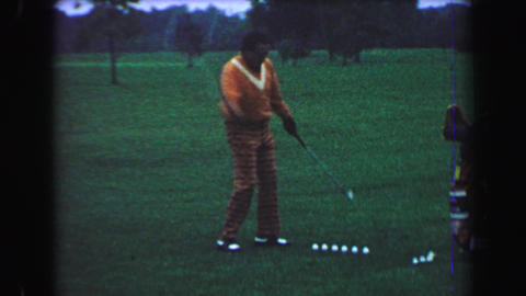 1969: Golfing trick shot professional performance man alternates one handed hits Footage