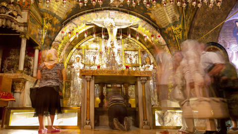 Tracking footage of pilgrims at an altar in the Church of the Holy Sepulchre. Cr Footage