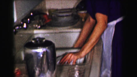 1958: Woman hand washing dishes after dinner in kitchen sink Footage