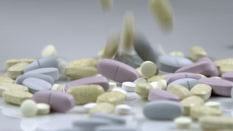 Supplement pills dropping into a pile Footage