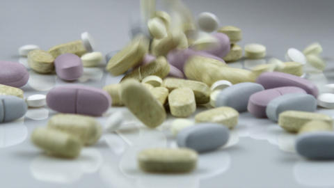 Supplement pills falling onto a pile Footage