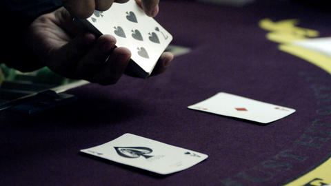 Dealer showing off a card deck with two cards placed on the purple table Footage