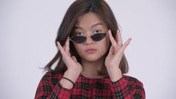 Face of young beautiful Asian businesswoman peeking over sunglasses Footage