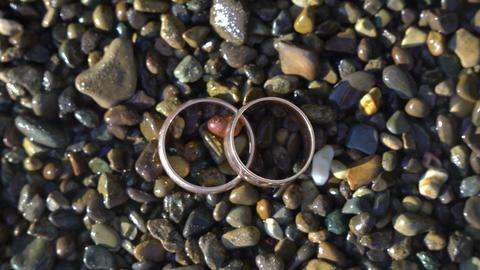 Two gold wedding rings lying on beach stones shining on sun light close up macro Footage