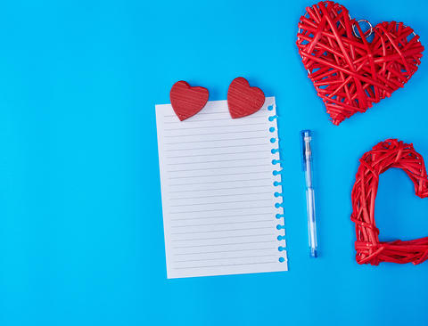 wooden wicker red heart and an empty white sheet of notepad Fotografía