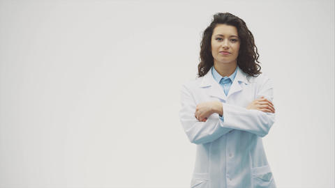 Portrait of happy young smiling girl doctor. Dressed in a white robe. Evenly Footage