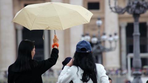 A woman uses an umbrella to shield another woman with a camera in Vatican City Footage