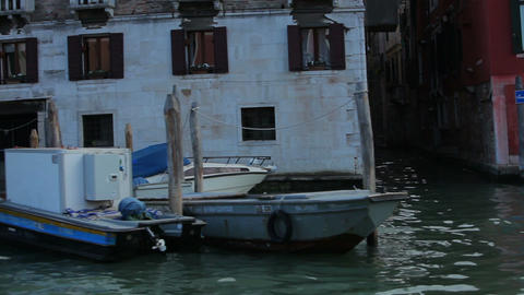 Shot of Italian canal with boats tied to wooden posts Footage