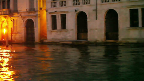 Passing by buildings with decorated pillars while boating through Venice at nigh Footage