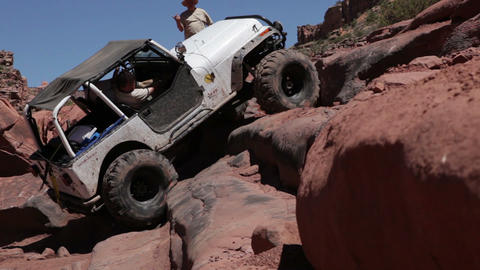 White jeep spins tires, climbs slope Footage