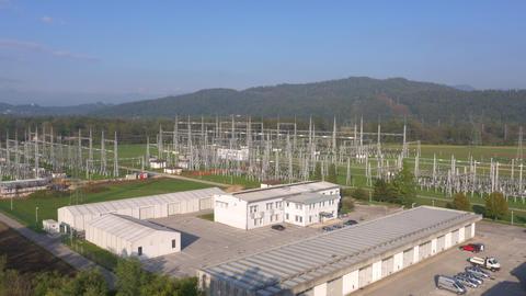 Aerial - Flyover treetops towards power substation Footage
