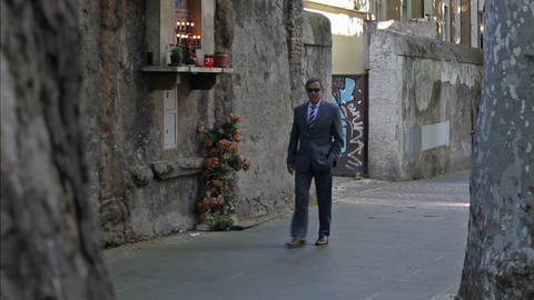 ROME - CIRCA MAY 2012 A sunglasses-wearing man walks down a sidewalk circa May 2 Footage