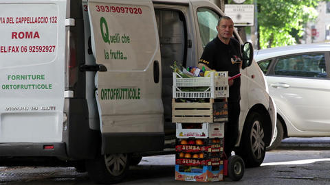 A delivery man stands next to his delivery van and a stack of fruit in Rome, Ita Footage