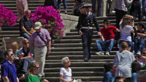 A uniformed man walks down the Spanish Steps, which are crowded with tourists. R Footage