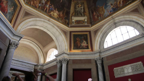 Footage tilts down from a ceiling fresco in the Vatican Museums to tourists taki Footage