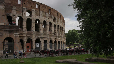 View of the Colosseum with tourists and horse carriages seen in front Footage