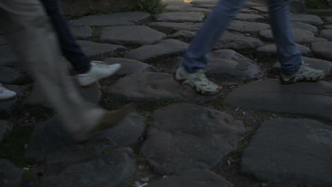 Feet walking across cobblestones Footage